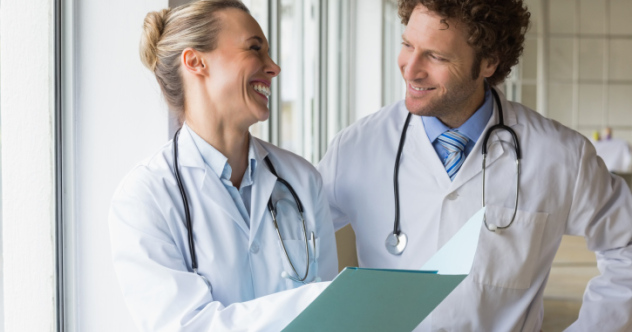 Happy doctors discussing over file