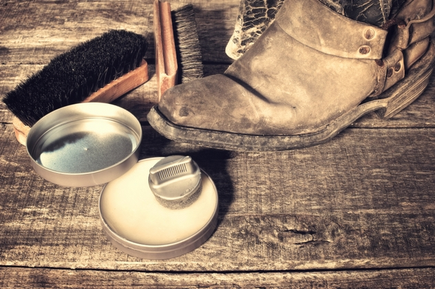 Shoe wax, boot and brushes on wooden surface