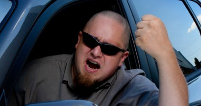 An angry driver shakes his fist out the window of his vehicle.