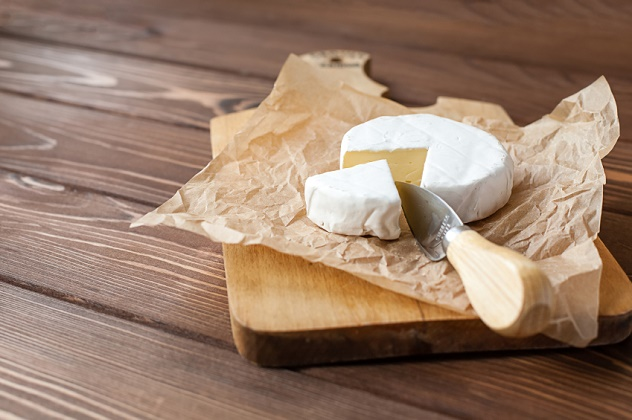 piece of Camembert with knife