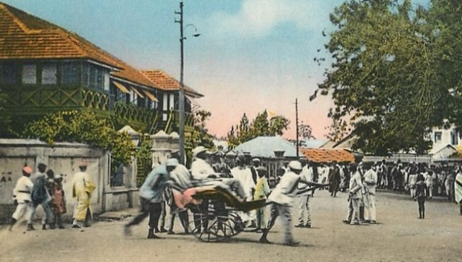 Possible Iwofa driving man riding on a chariot in front of Lagos police station, southern Nigeria. Early 1900s. Servitude like this was acceptable till the fist half of the 20th Century.