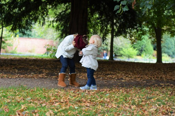 Autumn leaves and two sisters playing