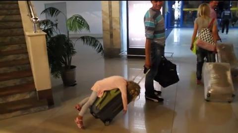 【動画】長旅で疲れた少女、パパのキャリーバッグの上で力尽きる