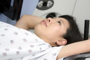 Asian woman receiving radiation treatment