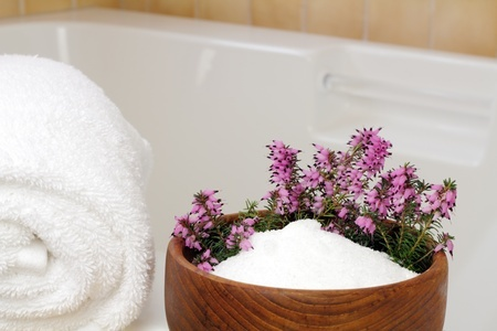 11186670 - fresh pink purple heather flowers in a teak wood bowl with epsom salts on the edge of a bathtub with a rolled up white towel ready to take a relaxing bath.