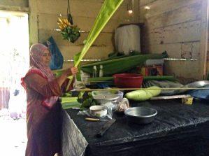 Nyak Wa Marlaini sedang menyiapkan daun untuk membuat timphan