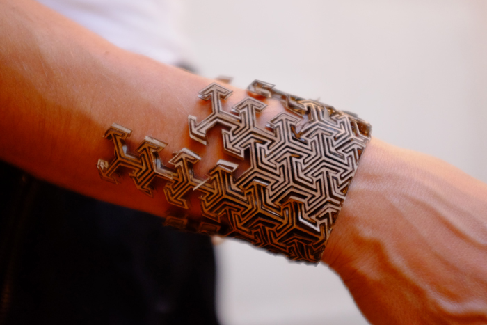A slightly different design of a laser cut cardboard bracelet. The back laces up with twine.