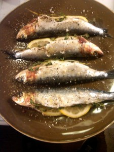 Grilled sardines on a brown plate.