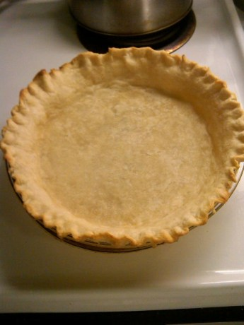Partially baked pie crust on a white table.