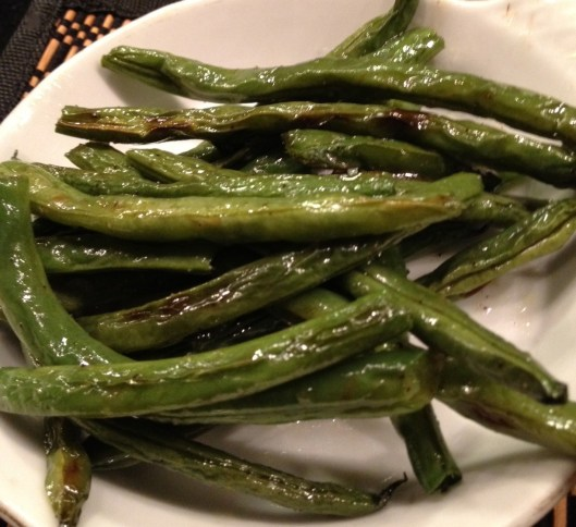 Over roasted green beans in a white bowl.