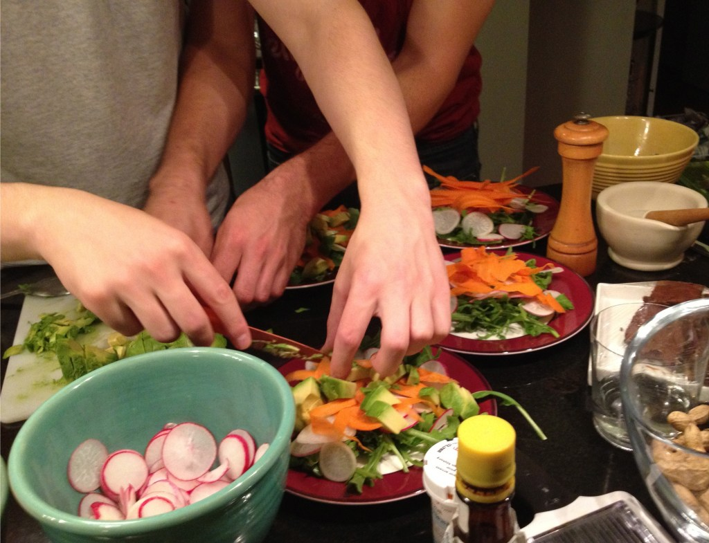 Making an arugula salad with radishes, carrots, avocado, and white wine and olive oil vinaigrette.