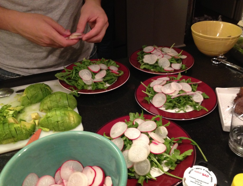 Arugula salads with radishes on red places.