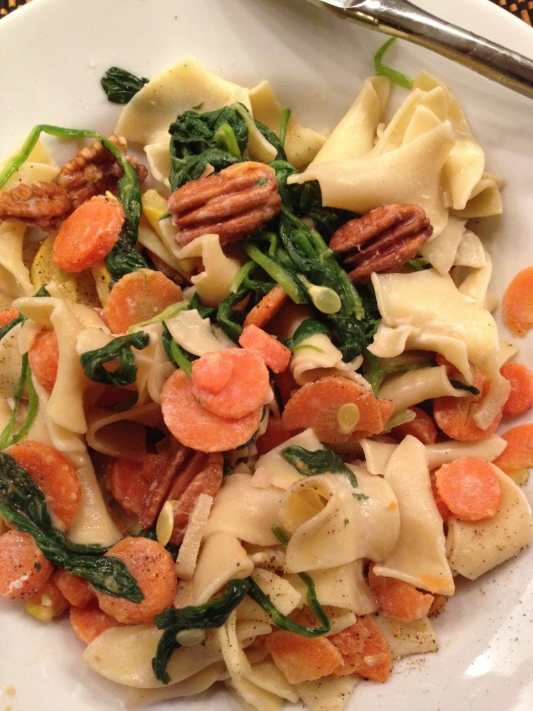 Vegetarian pasta with walnuts and spinach on a white plate.