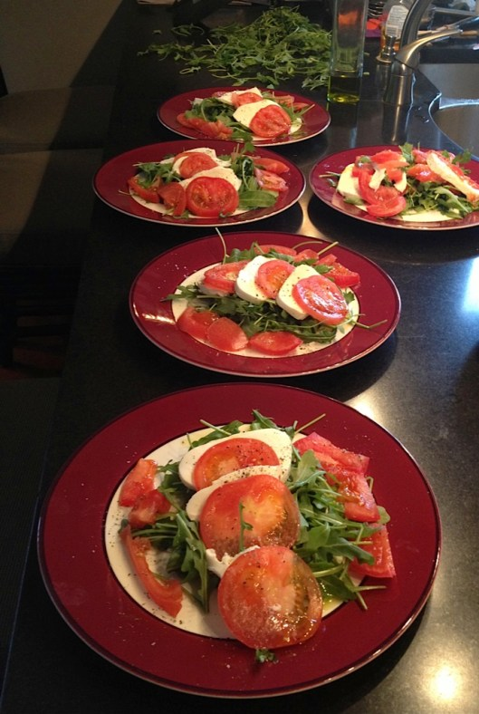 Mozzeralla, tomato, baby arugula and olive oil salads on a burgandy rimmed plate from Pottery Barn.