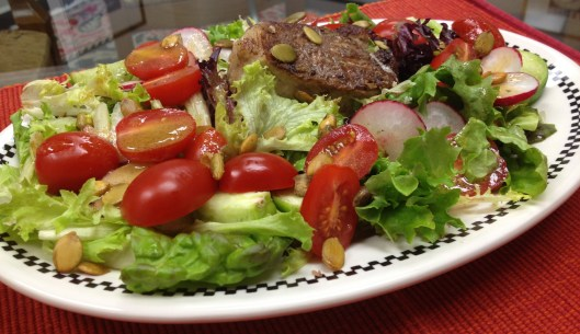 Frisee lunch salad with pork chop, tomatillos, tomatoes, radishes, and toasted pepito seeds.