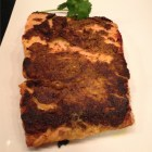Sesame and curry crusted whole salmon piece on a white platter.