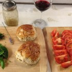 Chopped basil and thyme, hearty rolls and sliced and quartered tomatoes on wooden cutting boards.