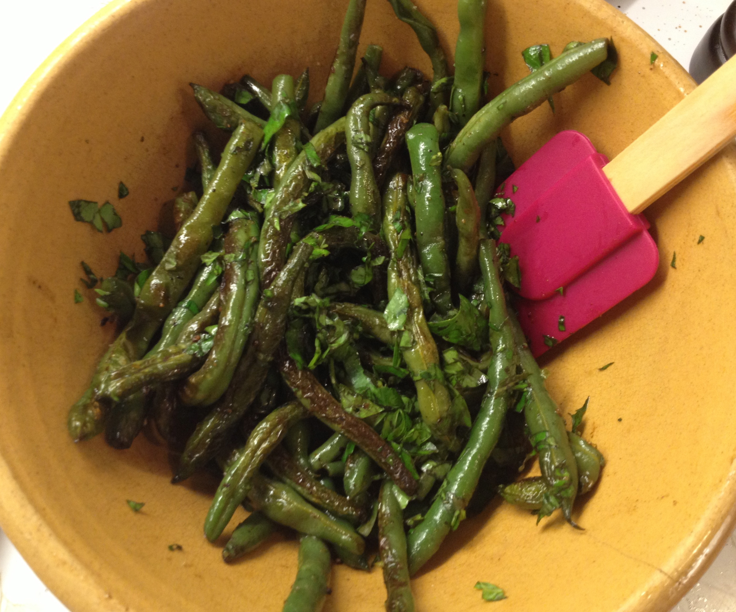 Green bean recipe using fresh basil in a yellow ware bowl with a maroon spatula.