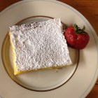 Lemon bars on a off white china plate with a fresh strawberry in an overhead shot.