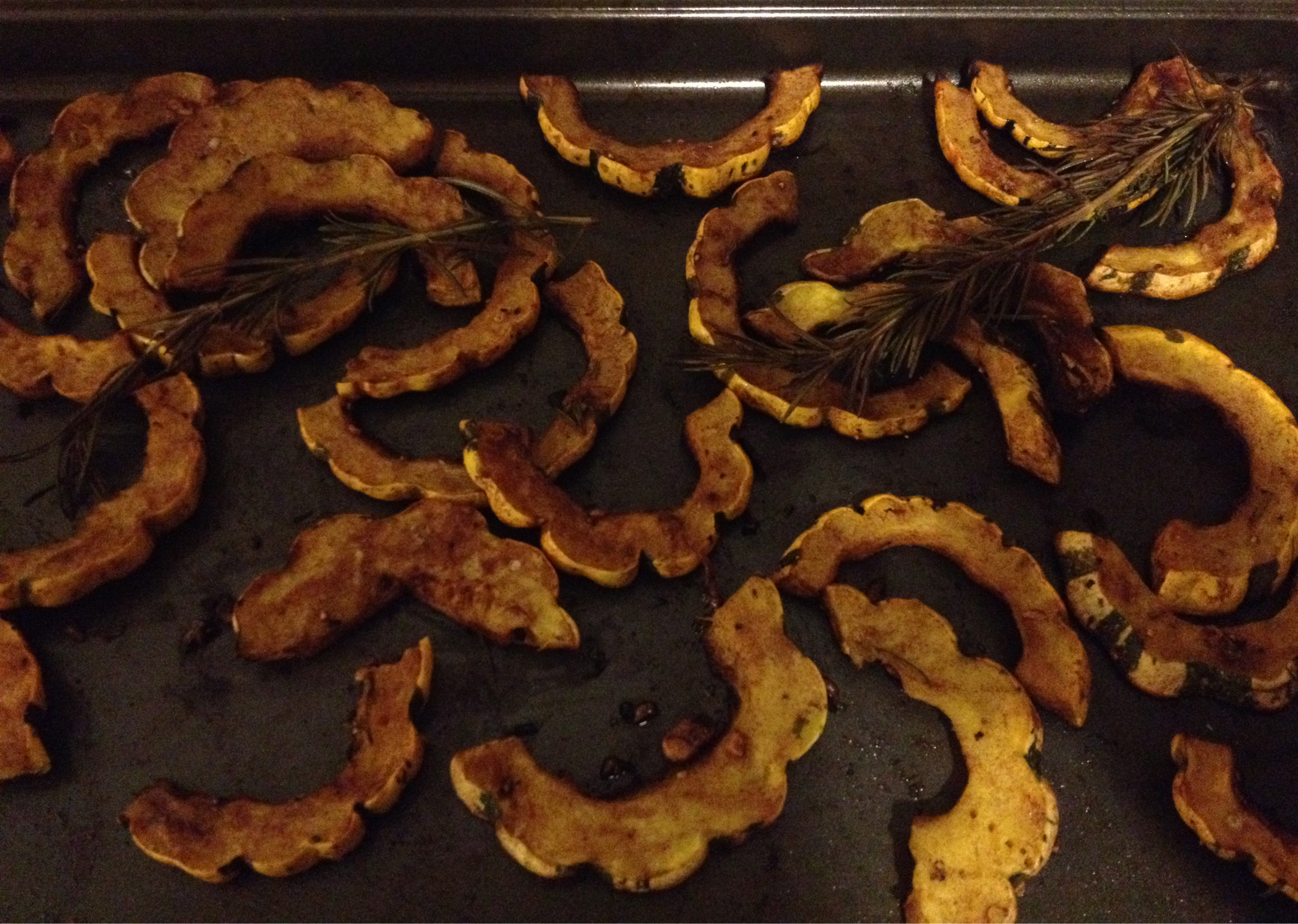 Roasted deicata squash on roasting pan.