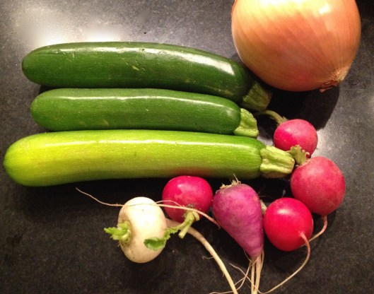 Raw zucchini, multi-colored radishes and a sweet Spanish onion on a black granite countertop.