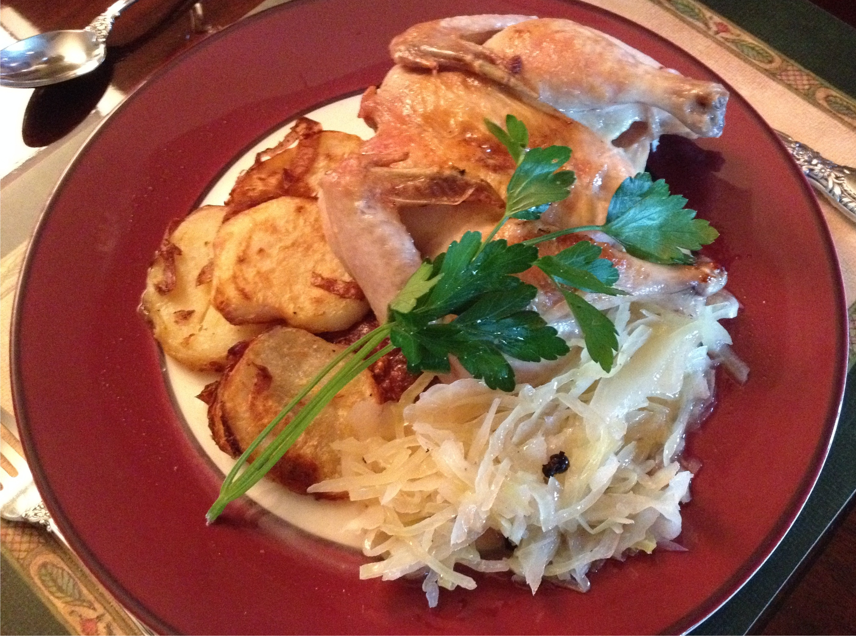 Roasted Cornish hens with sauerkraut and sliced roasted potatoes