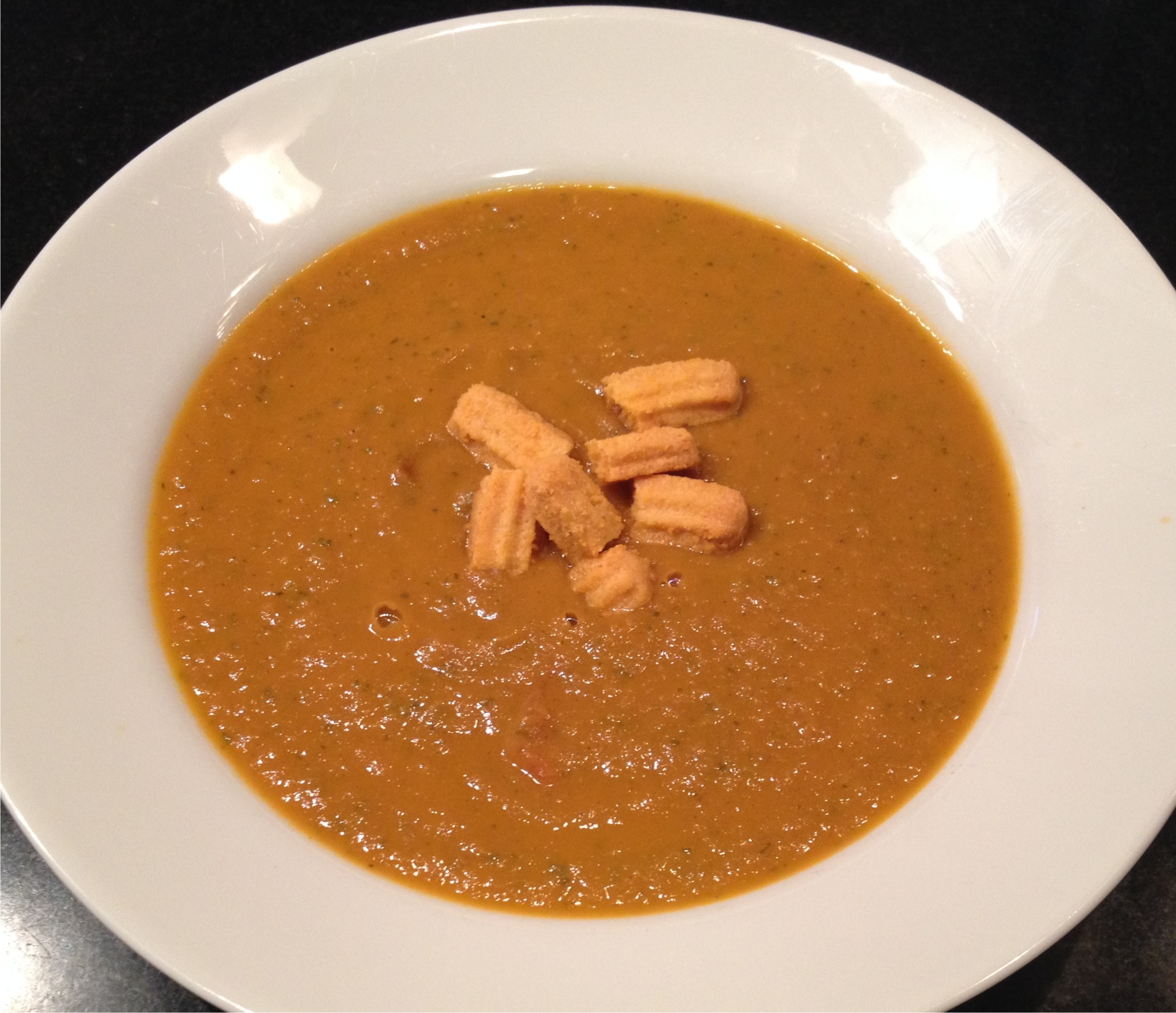 Smoked tomato soup with Neuskes Sausages and Flathaus Cheese Straw croutons in a white rimmed bowl