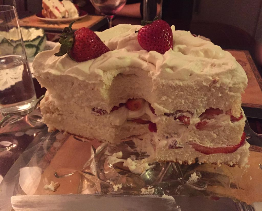 Angel food cake cut with whipped cream and strawberries.