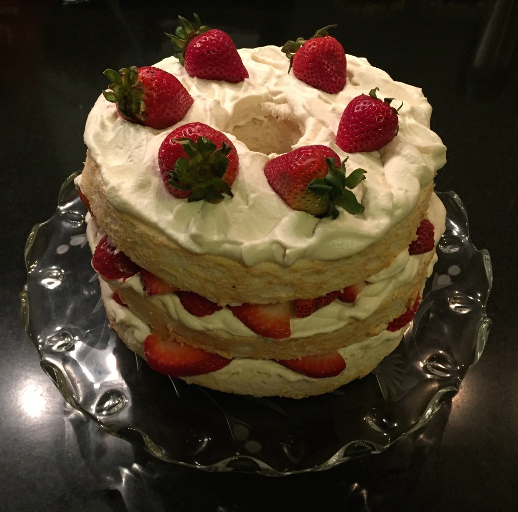Angel food cake with whipped cream and strawberries.