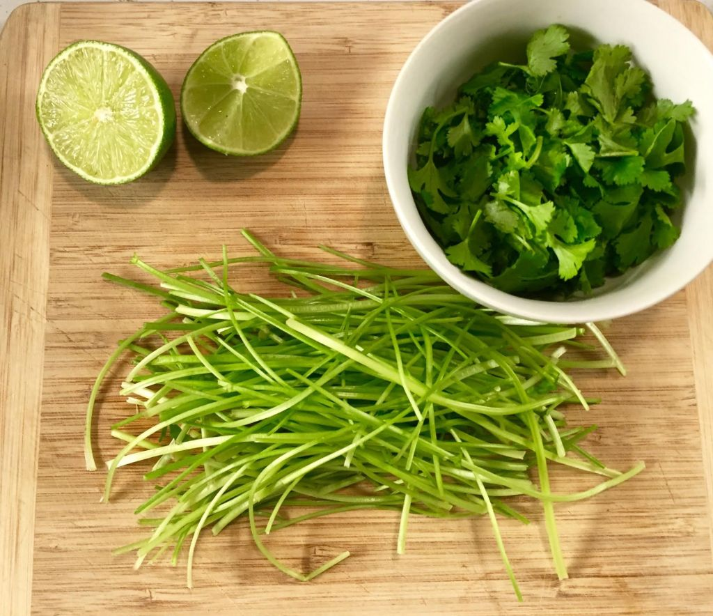 Cilantro stems, leaves and a cut lime on a wooden cutting board.