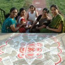 Members of Tamil Makkal Mandram, Inc. seated below a kolam drawn by KarthigaiPriya Govindarajan, (far left).