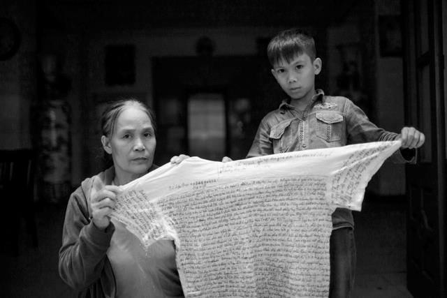 Mẹ và con trai tử tù Lê Văn Mạnh với chiếc áo in lá thư mà Lê Văn Mạnh gửi từ trong tù ra. Nguồn: Facebook Vụ án tử tù Lê Văn Mạnh.