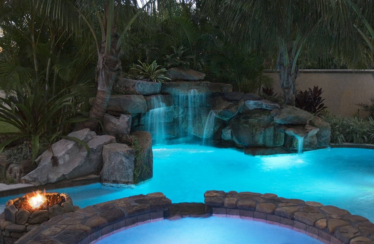 Lagoon pool with spa grotto waterfall and fire pit for Pool and firepit design