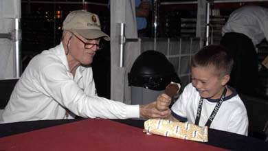 Paul Newman, founder of the Hole in the Wall Camps, and 'Paul', an eight-year-old Victory Junction Gang camper, enjoy ice cream bars during the Las Vegas Champ Car 400.