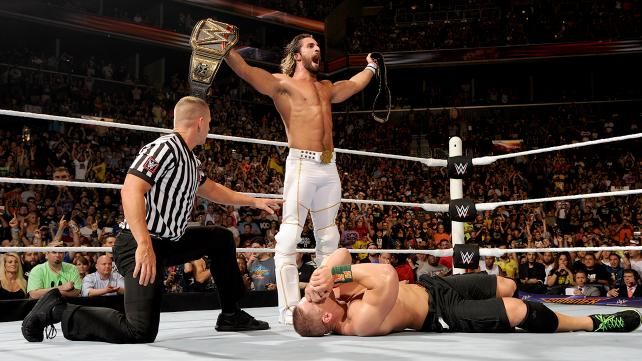 WWE Summerslam 2015 -Seth Rollins stands with both titles