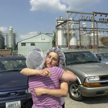 A FINAL GOOD-BYE - Maria Fontes, right, of Lincoln, and Lucy Amaral, of East Providence, leave the former Nyman Manufacturing Co., in East Providence Wednesday, their last day of work.
