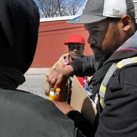 Ray Johnson, of Aids Care Ocean State, shows someone on a street in Central Falls an overdose prevention kit contaiing naloxone and needles. In the background is Keith Thompson, a member of the team of outreach workers who look for people on the street who might use the kit to saves lives. The Providence Journal/Mary Murphy
