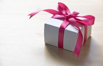 ラッピングされピンクのリボンがかかっている箱の写真