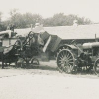 RIDING HIGH: Threshing machine, 1940s. Note the drum pulley on the tractor; It's the smaller cylinder between the front and rear wheels.