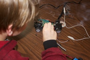 Matthias soldering leads into the PIC on the RC car so he can control with Arduino sketch.
