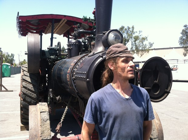 Kinetic Steamworks' Stephen Radmaker stands before a 1920 Case steam traction engine.