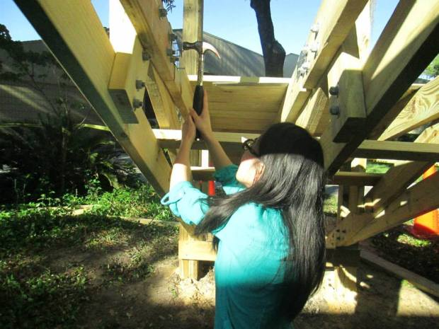 A student installs metal hurricane straps and metal plates all over the undercarriage with joist nails and screws for extra strength.