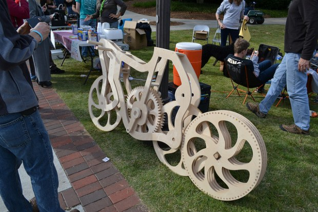 A complex CNC-cut wooden bicycle sits idle.