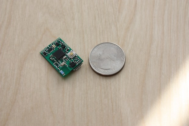 The MetaWear board next to a quarter for scale.