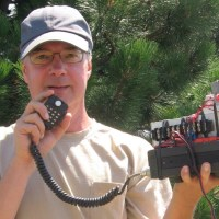 "Jon Platt, WØZQ, shows off his microwave ""handheld"" station - a complete transmitter and receiver package with the horn antenna built right in. With this simple station, Jon has made contacts hundreds of kilometers away by bouncing signals off of rain showers and other weather-related structures, such as temperature inversion layers. (Photo by Bruce Richardson, W9FZ, and provided courtesy of the ARRL)"