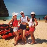 girls on the beach in krabi. three girls wearing hats.