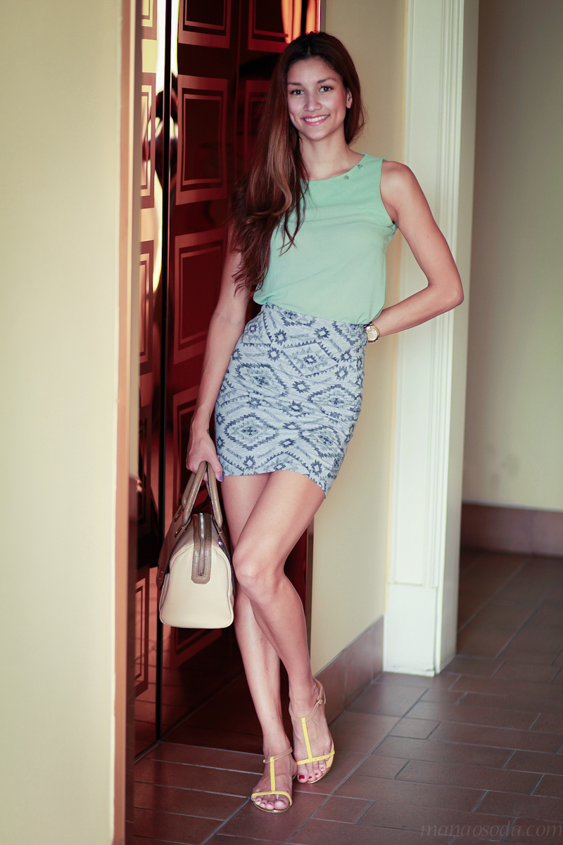 Holding charles & keith bag. Pastel colored top. Wearing guess watch.