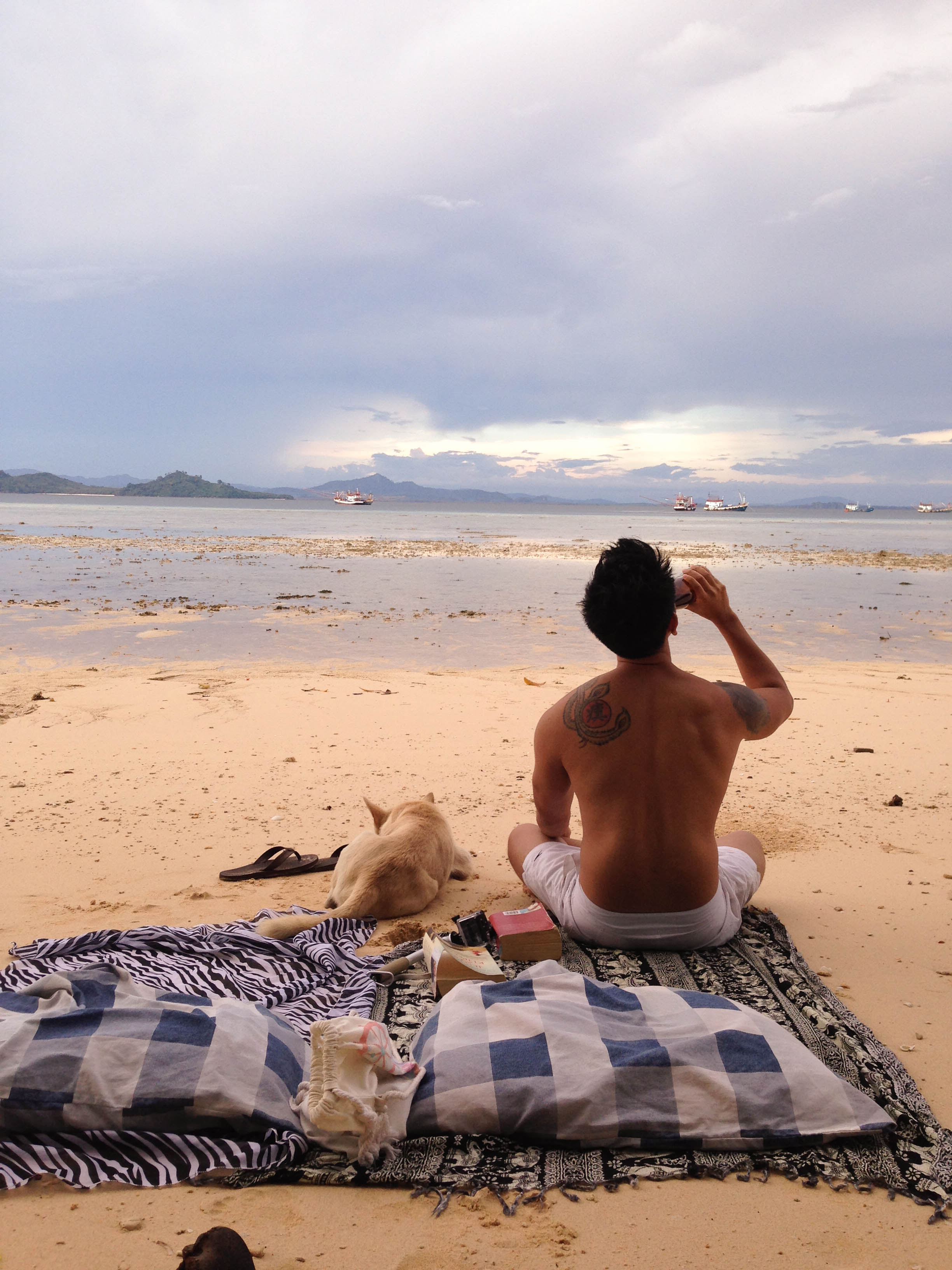 boy relaxing with beer and dog on koh kradan island