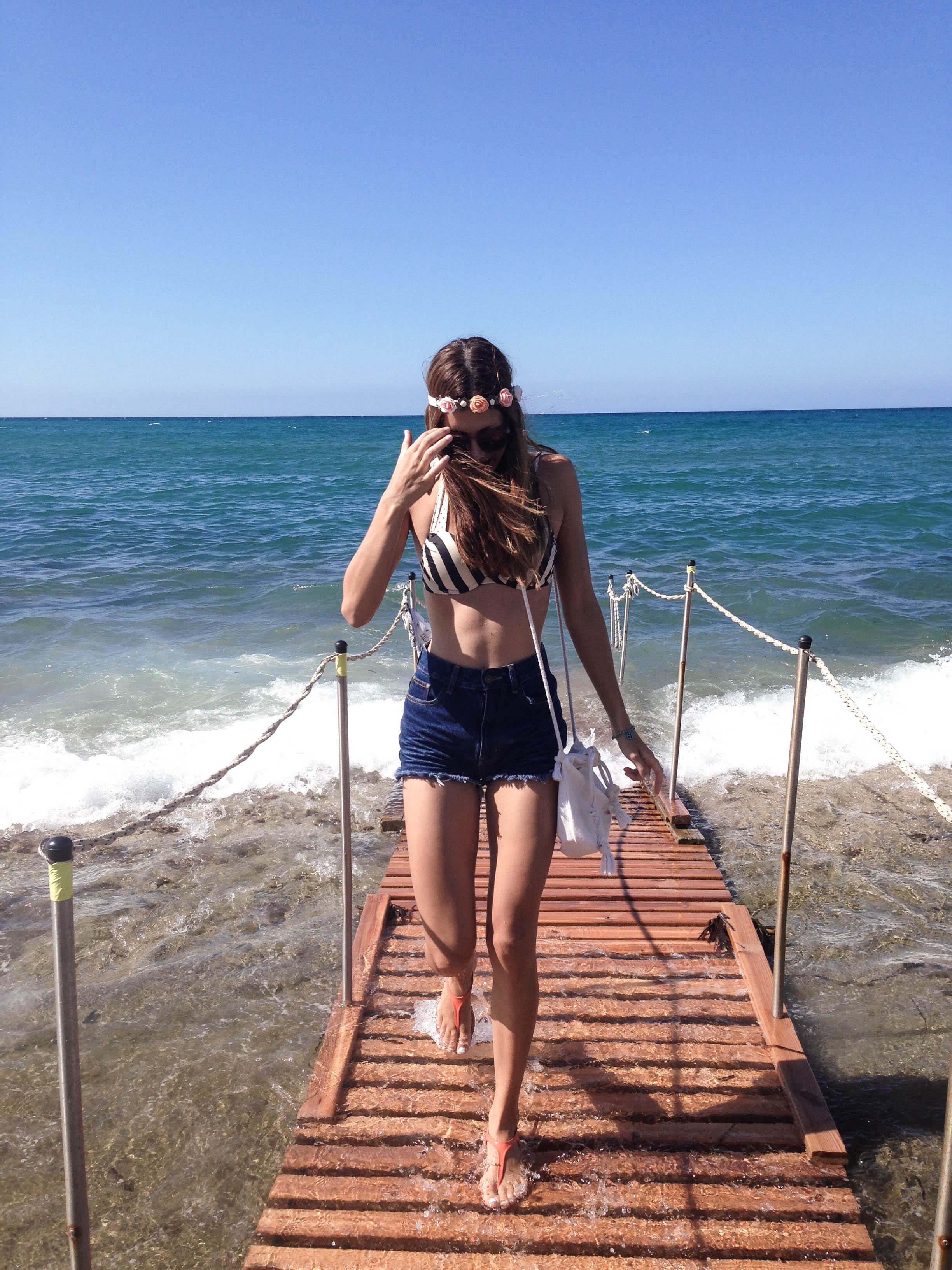 girl wearing flower hairband on the beach in platanias greece