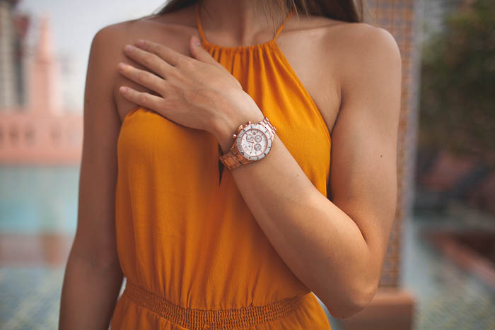 girl wearing orange suit wearing gold watch